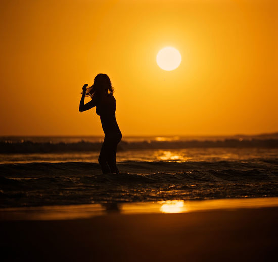 Sunset Silhouettes Sunset_collection Beach Beauty In Nature Bikini Horizon Horizon Over Water Land Leisure Activity Lifestyles One Person Orange Color Outdoors Real People Reflection Scenics - Nature Sea Silhouette Sky Standing Sun Sunset Sunsets Swim Water