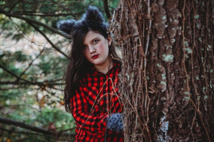 Portrait of beautiful young woman standing by tree trunk in forest