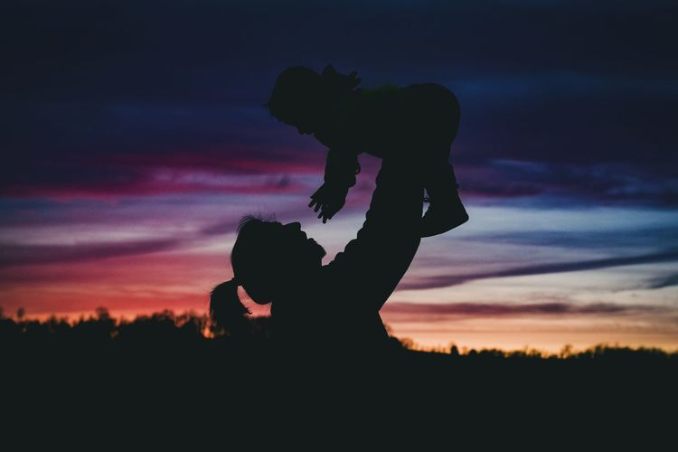 Silhouette mother playing with baby against sky during sunset