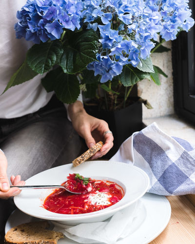 Midsection of woman holding red chili peppers in bowl on table