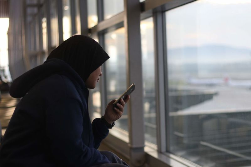 Woman wearing hijab while using mobile phone at airport