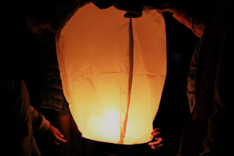 Midsection Of Male Friends Holding Illuminated Paper Lantern At Night