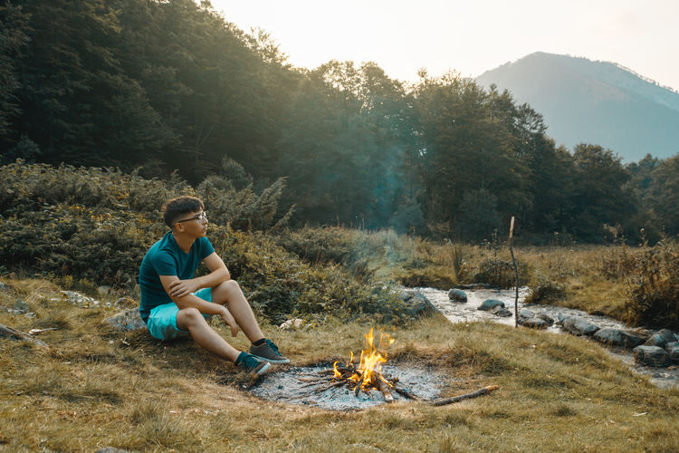 Man sitting on bonfire by trees