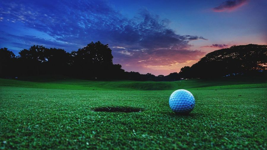 Golf ball on a golf course during sunset Plant Green Color Grass Sport Sky Golf Ball Ball Sphere Activity Golf Nature No People Golf Course Leisure Activity Tree Scenics - Nature Night Beauty In Nature Field Outdoors