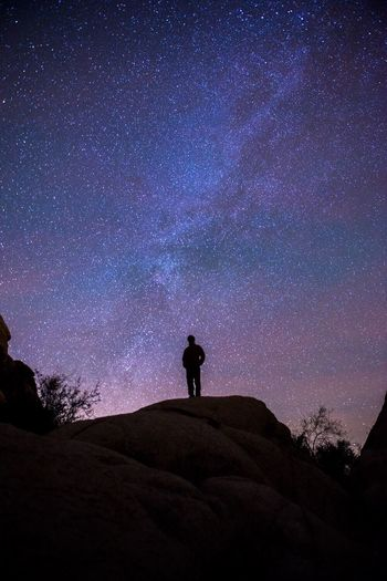 Low angle view of silhouette man standing on rocky mountains against star field at night