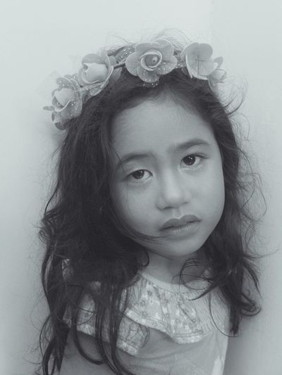 Close-up portrait of girl wearing tiara while standing against wall