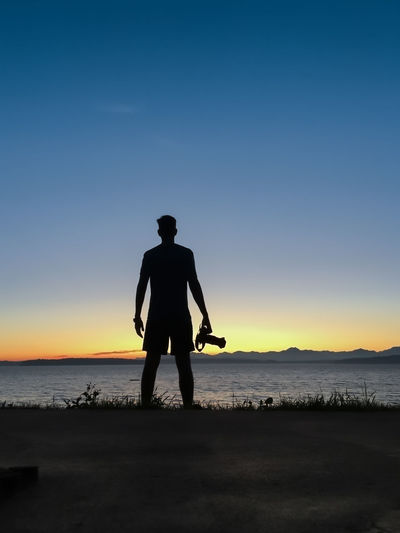 Silhouette man standing on shore against blue sky