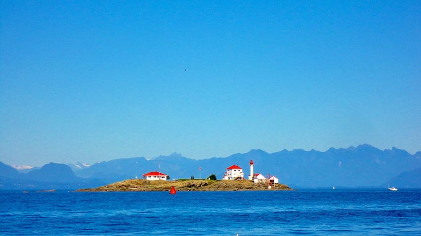 Island View  from Gabriola Island 🏘 British Columbia Canada Red Roofs Lighthouse Small Pretty Gabriola Island Blue Sea And Blue Sky Canadian Flag Island Life Beauty In Nature Mountain Range EyeEm Gallery 島 カナダ 灯台 Lighthouse_lovers Island Holiday BC Canada White Wall Small_world Anyone There?
