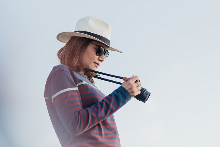 Side view of woman holding camera against sky