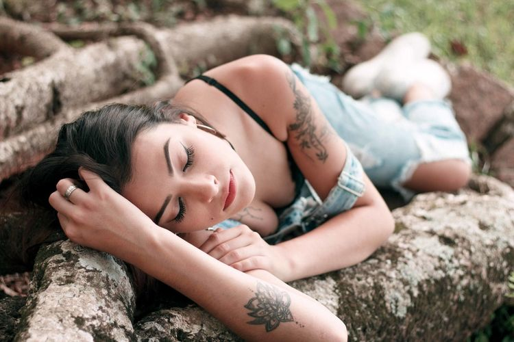Young woman lying on roots