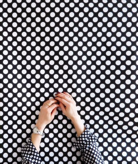 Human hands against spotted background