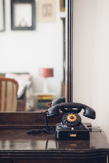 Rotary Phone On Table Against Mirror At Home