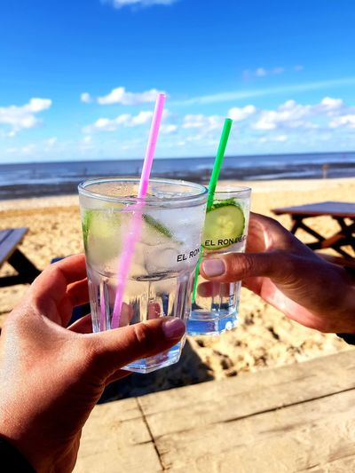 Cropped image of hand holding drink at beach against sky