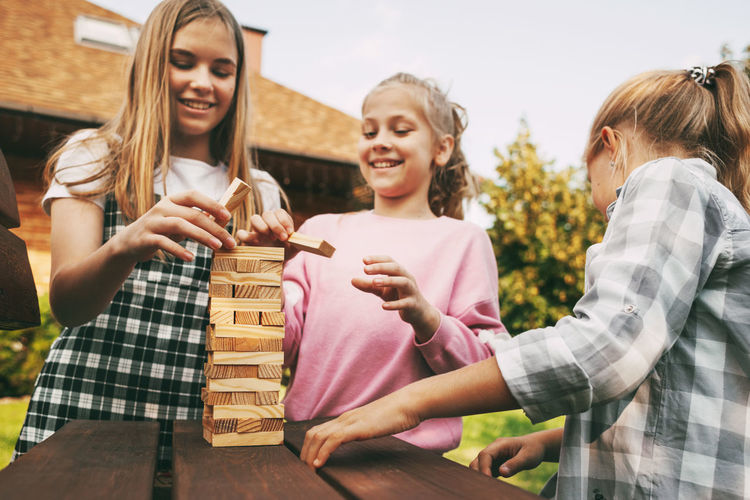 Three beautiful sisters are playing a wooden board game outdoors near their home.