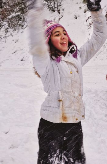 Smiling girl with arms raised standing in snow