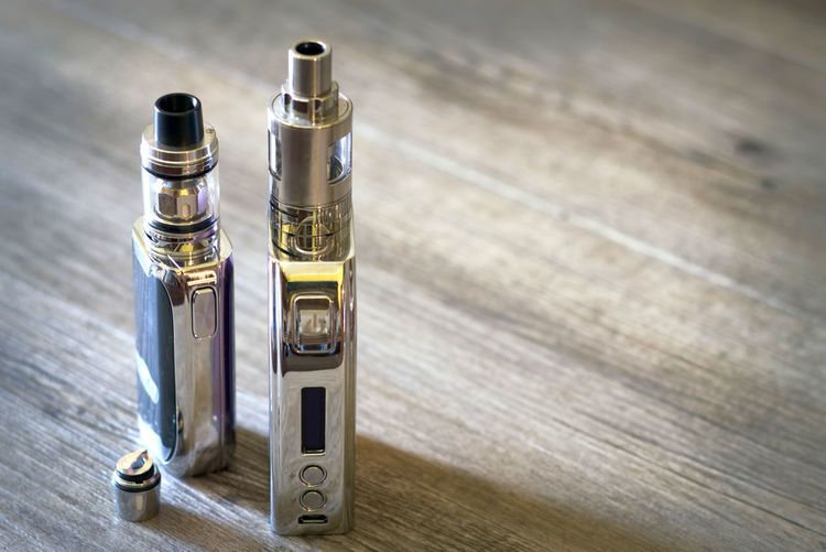 High Angle View Of Electronic Cigarette On Wooden Table
