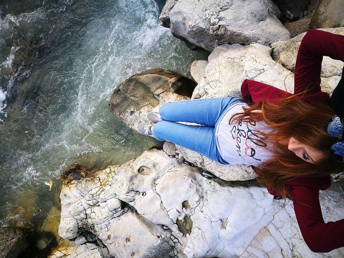 Woman sitting on rock over sea