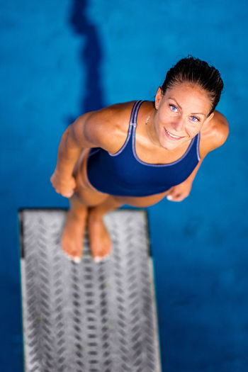 Female Diver Standing On The Jumping Board Diving Diver Swimming Pool Woman Water Sport Training Competition Young Exercising Diving Board Board Above Action Swimwear Blue Activity Muscular Build Extreme Sports Caucasian Ethnicity Athlete Standing Looking At Camera Smiling Portrait