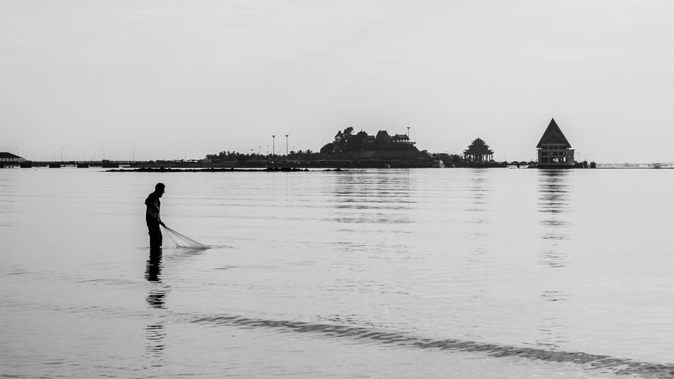 Fisherman with fishing net in sea Beauty In Nature Black And White Calm Casual Clothing Chonburi ,Thailand Day Fishing Fishing Net Island Landscape Leisure Activity Lifestyles Nature Ocean Outdoors Rippled Scenics Sea Sky Thailand Water