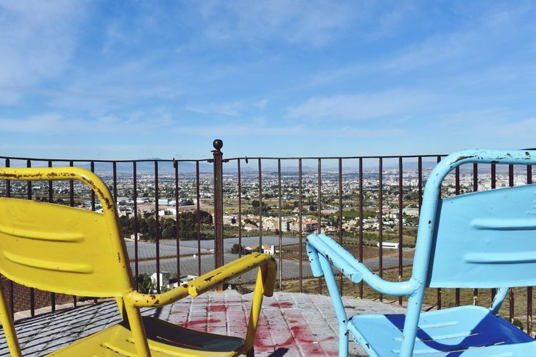 Metallic Chairs At Observation Point Against Blue Sky