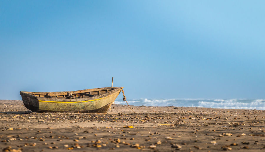 fishing boat on a beach in northern Peru Anchored Beach Beauty In Nature Clear Sky Copy Space Day Fishing Boat Horizon Horizon Over Water Land Low Tide Mode Of Transportation Moored Nature Nautical Vessel No People Outdoors Rowboat Sand Scenics - Nature Sea Sky Tranquility Transportation Water