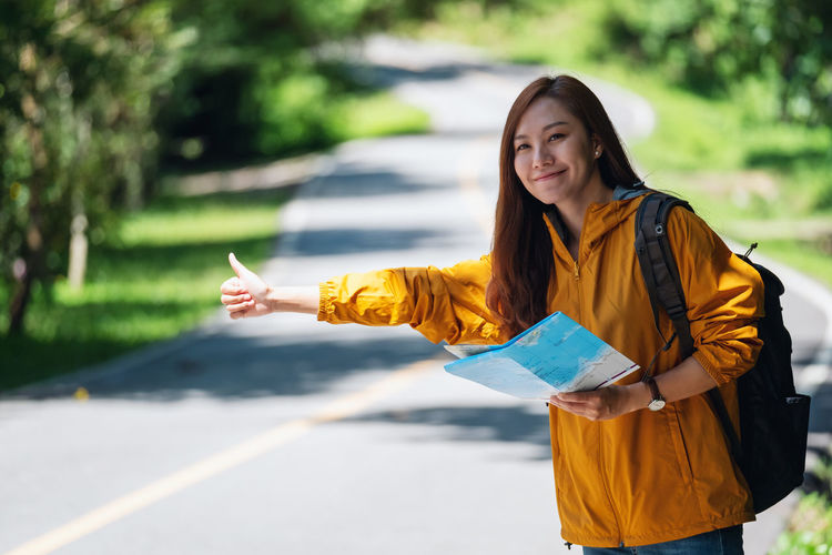 Portrait of a smiling young woman standing on road