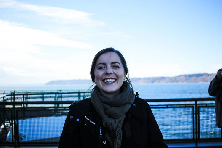 Portrait of smiling young woman standing in sea during winter