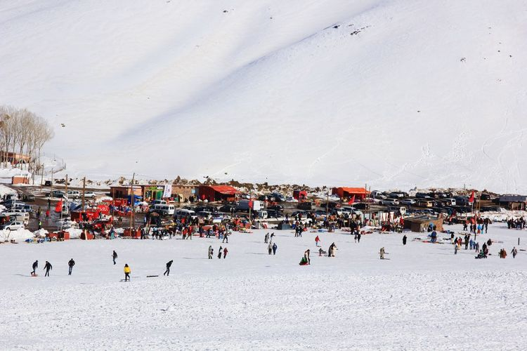 High angle view of people enjoying on snow field against mountain