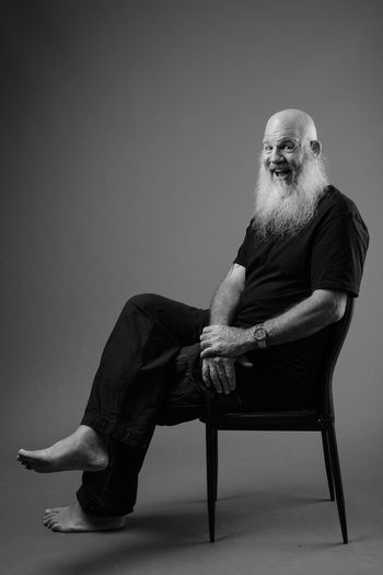 Portrait of man sitting on chair against wall