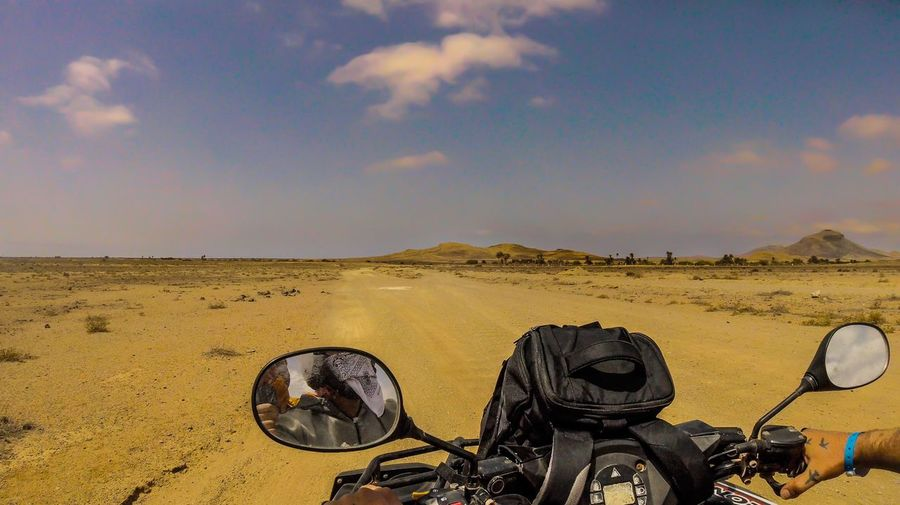 Bicycle parked on desert land against sky