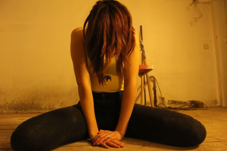 Sad woman sitting against wall at home