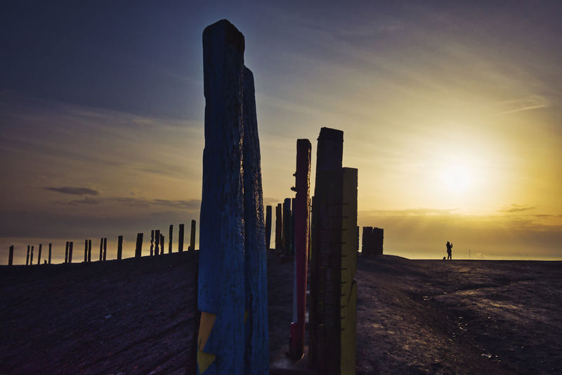 Wooden posts on hill against sky during sunrise