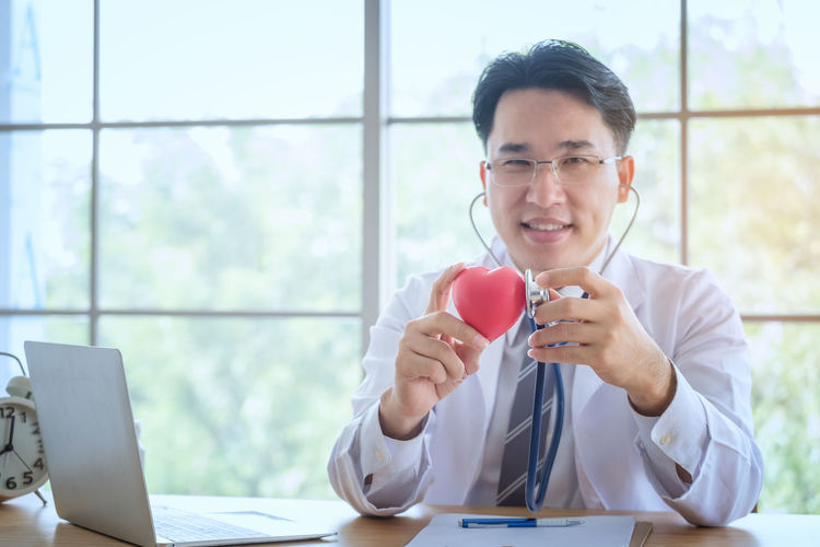 Heart in the hands of the doctor with stethoscope who mediates health. Love concept. Health concept. selective focus. Adult Close-up Communication Day Desk Eyeglasses  Front View Haert Holding Indoors  Office One Person People Sitting Technology Young Adult