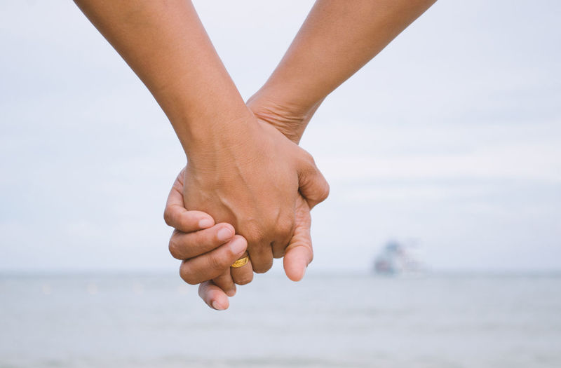 Couples hold hands at the sea. Accompanied Care Engaged Lover Promise We Along Attend Binding Chain Close Up Control Hand Hold Hands Human Hand Join Leisure Activity Lifestyles Nature Outdoors Sea Sky Together Us Water