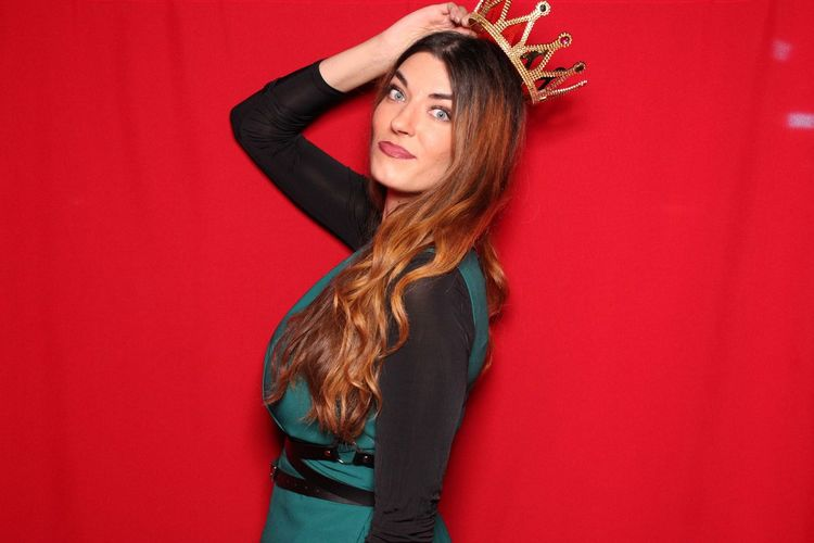 Portrait Of Young Beautiful Woman Wearing Crown Standing Against Red Background