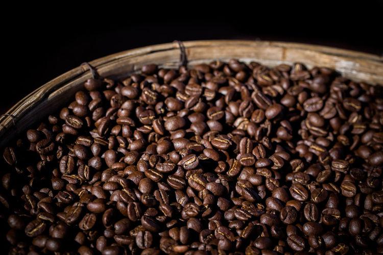 Close-Up Of Roasted Coffee Beans In Container Against Black Background