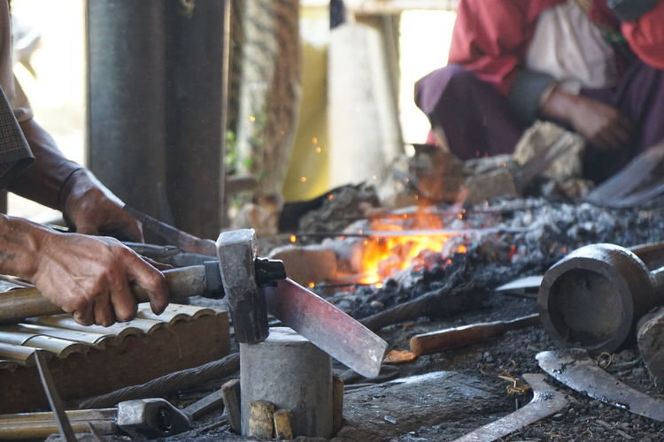 Cropped Image Of Blacksmith Working By Fire