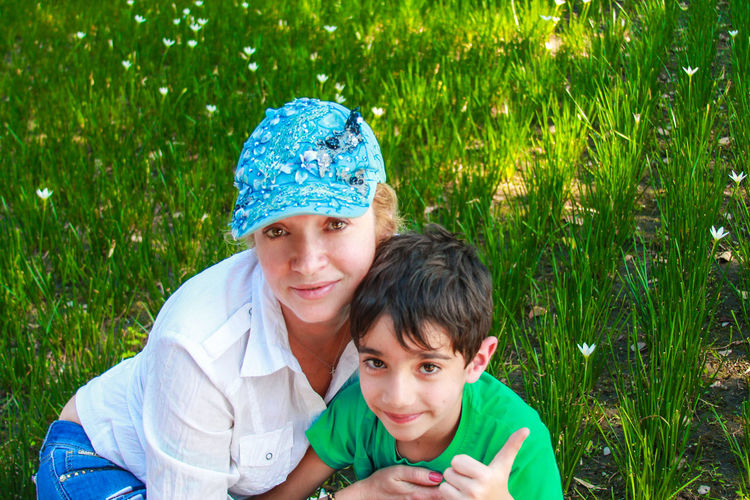 Portrait of smiling mother with son sitting on grassy field