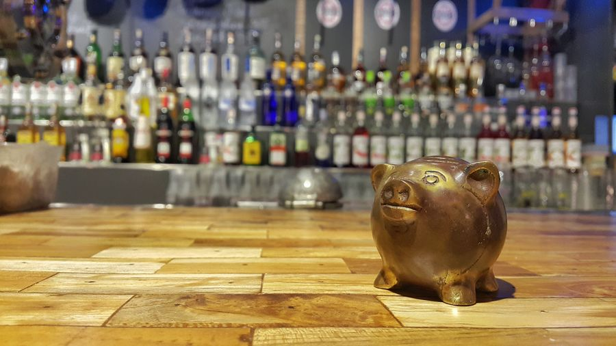 Piggy Bank Sculpture Toy on Bar Table of Restaurant with Liquor Bottle at Background , Concept of Quit Drinking, Start Saving . Indoors  Close-up No People Money Wasting Time Gathering Habit Bad Damaged