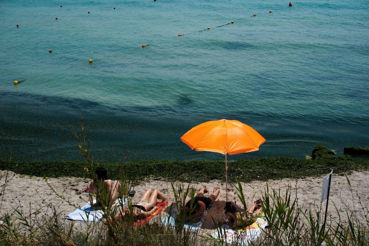 People and orange parasol at beach