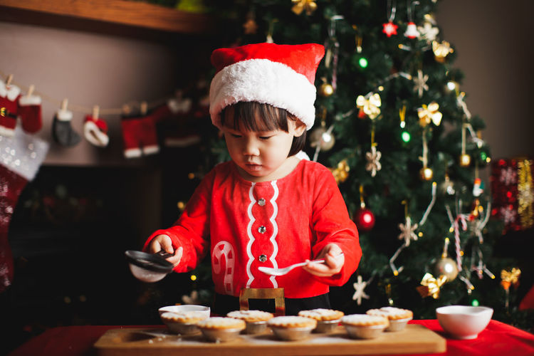 Girl preparing cookie at home during christmas