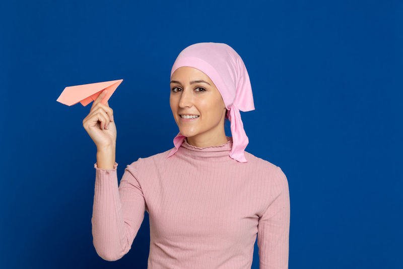 Portrait of smiling young woman holding paper airplane against blue background
