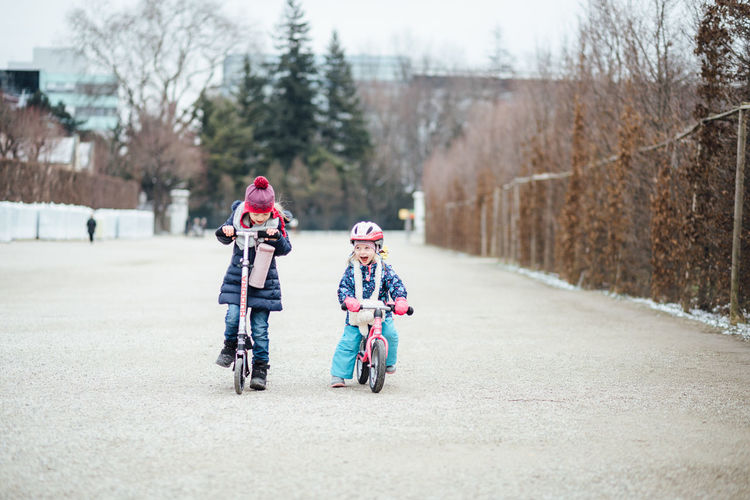 Child Transportation Childhood Real People Full Length Sport Two People Helmet Togetherness Day Lifestyles Ride Family Riding Headwear Outdoors Sister Warm Clothing Scooter Outdoor Activity Girls