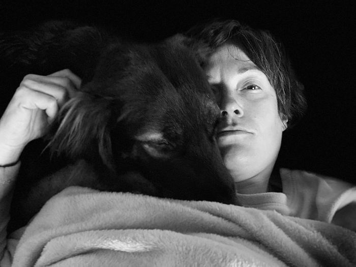 Close-up portrait of woman with dog against black background