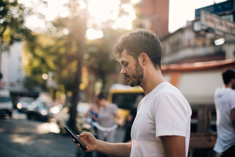 Young man looking at mobile phone in city