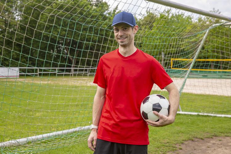 Portrait of man holding soccer ball in field