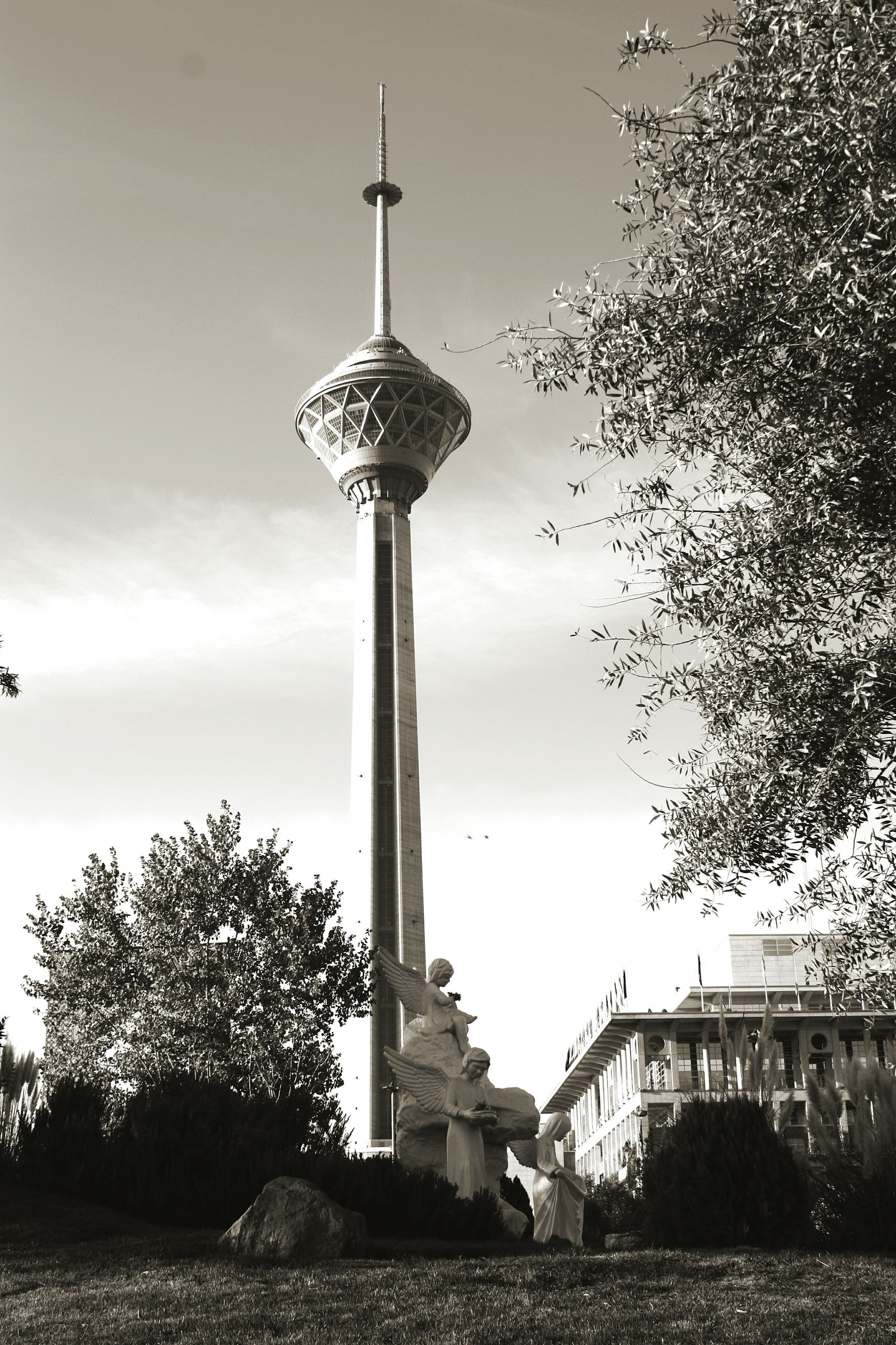 tree, tower, sky, communications tower, built structure, architecture, tall - high, building exterior, low angle view, communication, guidance, cloud - sky, travel destinations, lighthouse, spire, culture, day, fernsehturm, no people, outdoors