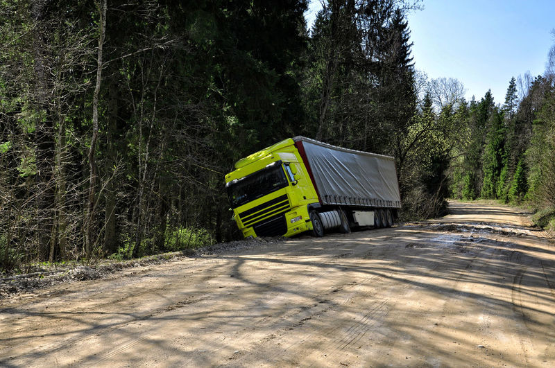 Yellow truck crashed to the forest road. Accident Automobile Autumn Crask Damaged Danger Day Destroyed; Forest Nature No People Outdoors Scenics Sky SP Transportation Tree