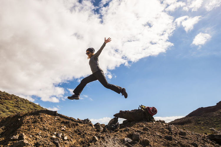 Low angle view of woman jumping on rock against sky