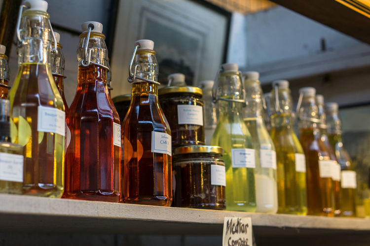 Close-Up Of Drinks In Glass Bottles On Shelf